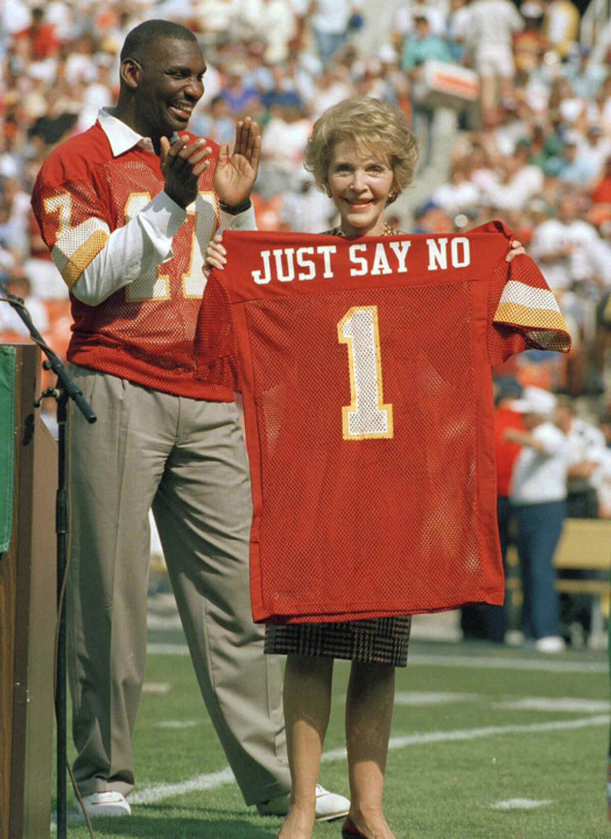 FILE - In this Oct. 2, 1988 file photo, Washington Redskins injured starting quarterback Doug Williams stands behind first lady Nancy Reagan holding a jersey he gave her before a football game against the New York Giants at RFK Stadium in Washington, D.C. The ceremony marked the Redskins' salute to her