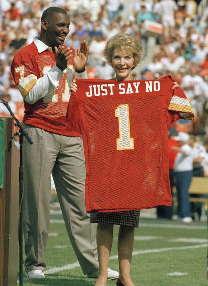 "FILE - In this Oct. 2, 1988 file photo, Washington Redskins injured starting quarterback Doug Williams stands behind first lady Nancy Reagan holding a jersey he gave her before a football game against the New York Giants at RFK Stadium in Washington, D.C. The ceremony marked the Redskins' salute to her ""Just Say No"" anti-drug campaign. Reagan, who died Sunday, March 6, 2016, is perhaps best known for her ""Just Say No"" to drugs and alcohol campaign. Three decades after the campaign's heyday, prevention experts credit it with spawning a new generation of research into the best ways of reducing drug abuse. But they also say that many of the fear-based tactics it embraced didn't work.(AP Photo/Doug Mills, File)"