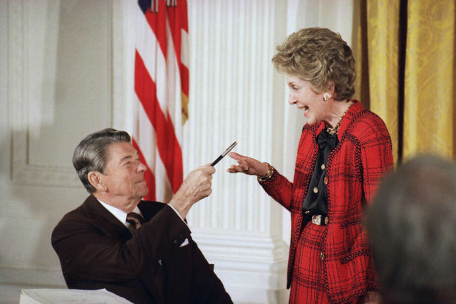 "FILE - In this Nov. 18, 1988 file photo, former President Ronald Reagan hands a pen to then first lady Nancy Reagan after he signed a major anti-drug bill at a White House East Room ceremony in Washington. Reagan dedicated the bill to Nancy, who has led a ""Just Say No"" campaign among America's youth, and gave her the pen he used to sign the bill with. Nancy Reagan, who died Sunday, March 6, 2016, is perhaps best known for her ""Just Say No"" to drugs and alcohol campaign. Three decades after the campaign's heyday, prevention experts credit it with spawning a new generation of research into the best ways of reducing drug abuse. But they also say that many of the fear-based tactics it embraced didn't work. (AP Photo/Ron Edmonds, File)"