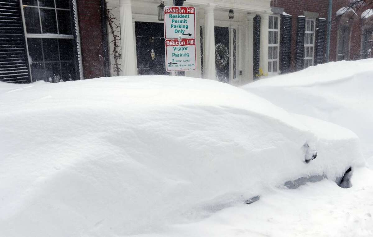 Snow covers parked cars on Beacon Hill in Boston, Sunday, Feb. 15, 2015. A blizzard warning was in effect for coastal communities from Rhode Island to Maine, promising heavy snow and powerful winds to heap more misery on a region that has already seen more than 6 feet of snow in some areas. (AP Photo/Michael Dwyer)