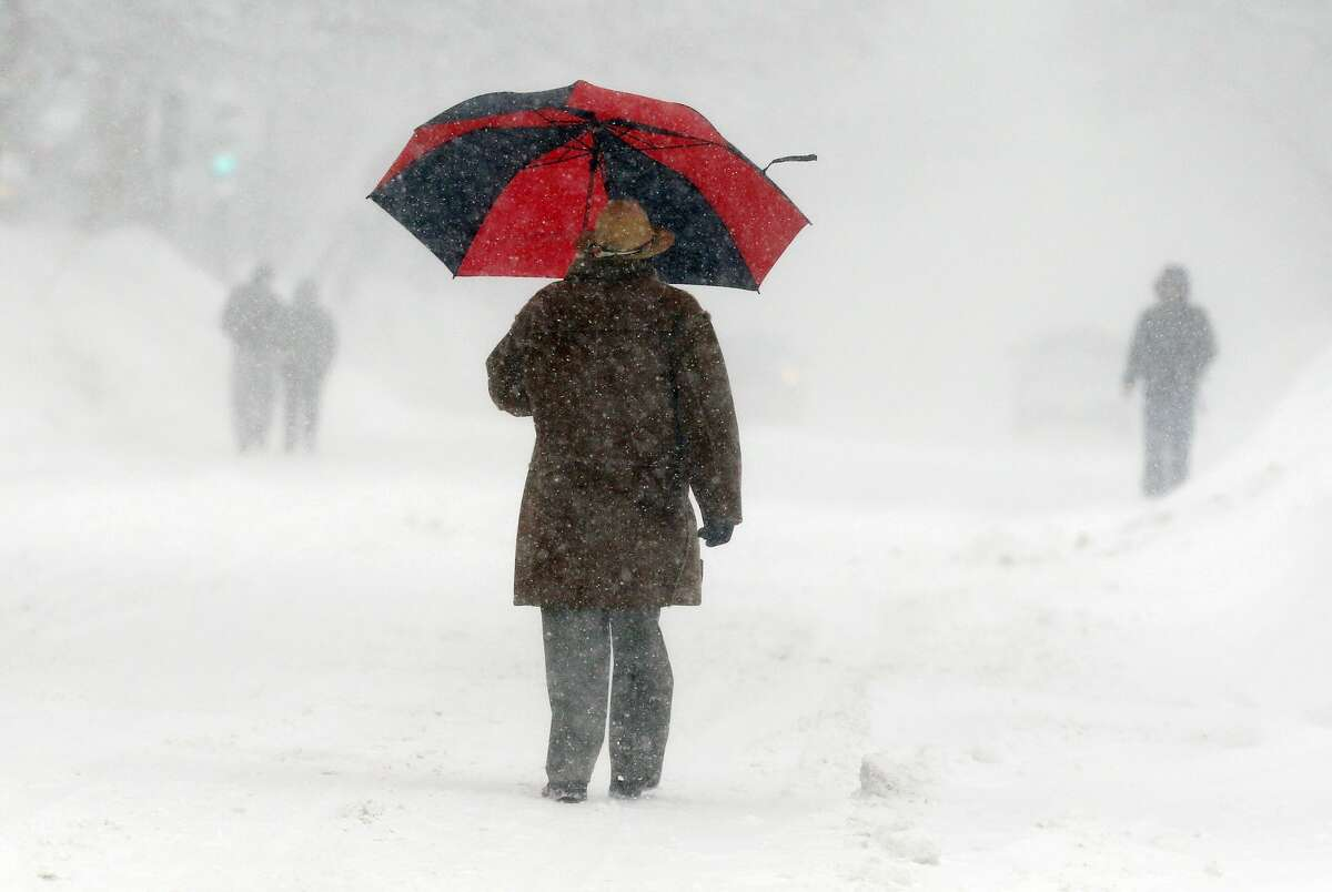 Pedestrians walk through blowing snow in the East Boston neighborhood of Boston, Sunday, Feb. 15, 2015. A storm brought a new round of wind-whipped snow to New England on Sunday, accompanied by near-whiteout conditions and lightning strikes in coastal areas as people contended with a fourth winter onslaught in less than a month. (AP Photo/Michael Dwyer)