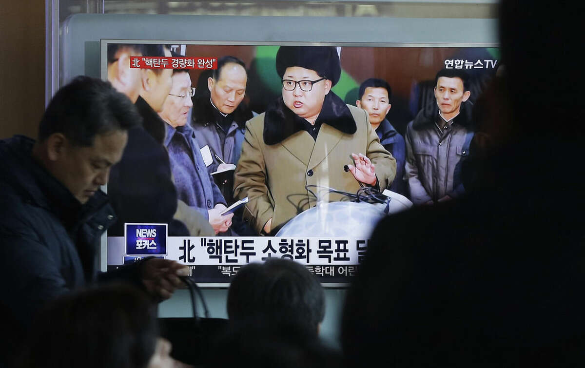 People watch a TV news program showing North Korean leader Kim Jong Un with superimposed letters that read: