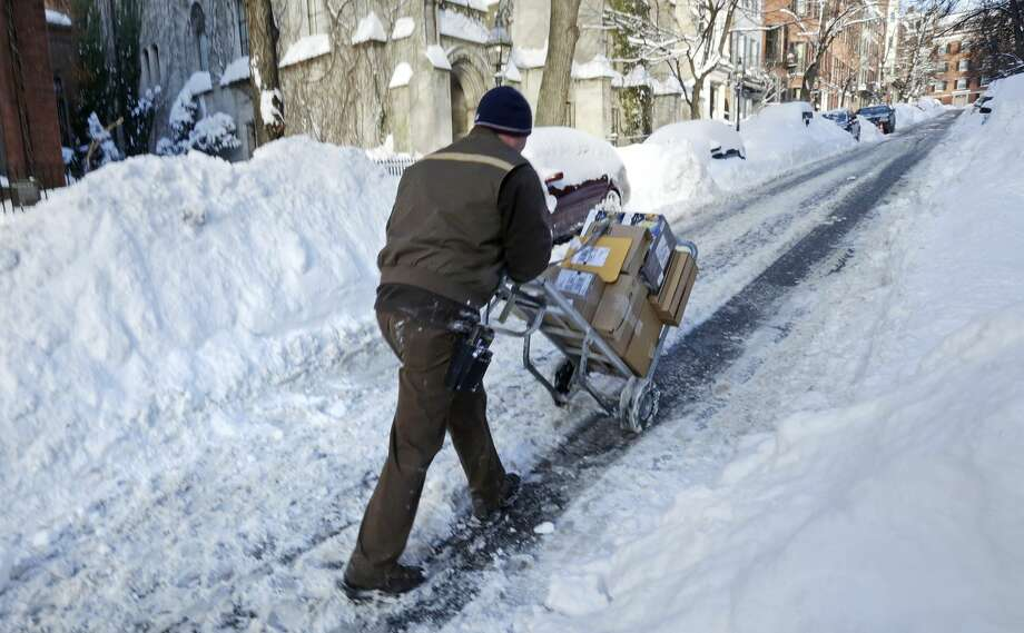 Joe Riley, of Braintree, Mass., pushes a hand cart up Beacon Hill while making deliveries in Boston, Tuesday, Feb. 3, 2015. Riley, a United Parcel Service driver, decided to make most of his deliveries on foot due to the 40 inches of snow the area has received this past week, causing gridlock in much of the city. (AP Photo/Charles Krupa)