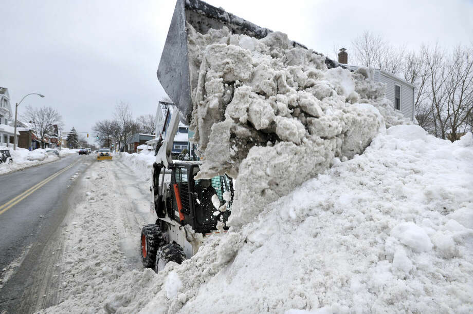 A worker uses a compact front-end loader to pile snow from a road to be removed by a dump truck near Davis Square in Somerville, Mass., Tuesday, Feb. 10, 2015. The third major winter storm in two weeks left the Boston area with another two feet of snow and forced the MBTA to suspend all rail service for the day. (AP Photo/Josh Reynolds)