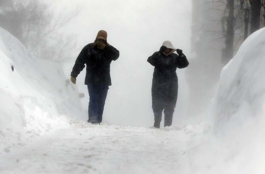 Lynn Cullins, right, and Kevin Burit, both of Caribou, Maine, walk through blowing snow on Beacon Hill in Boston, Sunday, Feb. 15, 2015. A blizzard warning was in effect for coastal communities from Rhode Island to Maine, promising heavy snow and powerful winds to heap more misery on a region that has already seen more than 6 feet of snow in some areas. (AP Photo/Michael Dwyer)