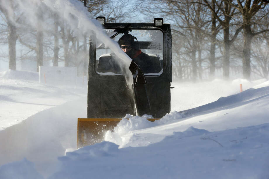 A worker clears snow from a walkway in Piers Park in the East Boston neighborhood of Boston, Monday, Feb. 16, 2015. New England remained bitterly cold Monday after the region's fourth winter storm in a month blew through. (AP Photo/Michael Dwyer)
