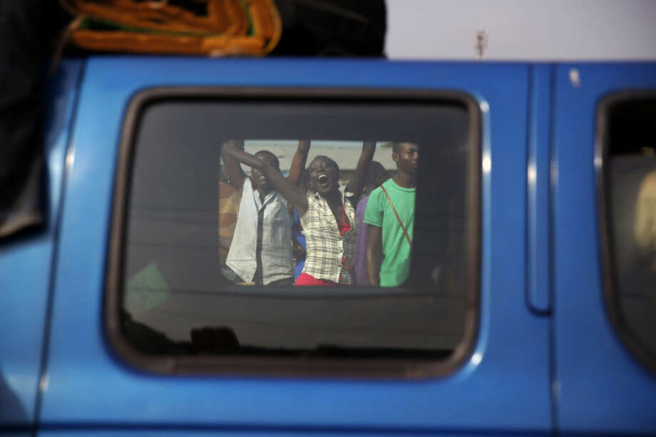 At PK12 Christians cheer as thousands of Muslim residents from Bangui and Mbaiki flee the Central African Republic Bangui in a mass exodus using cars, pickups, trucks, lorries and motorcycles, escorted by Chadian troops Friday Feb. 7, 2014. Tit-for-tat violence killed more than 1,000 people in Bangui alone in a matter of days in December. An untold number have died in the weeks that followed, with most of the attacks in Bangui targeting Muslims. (AP Photo/Jerome Delay)