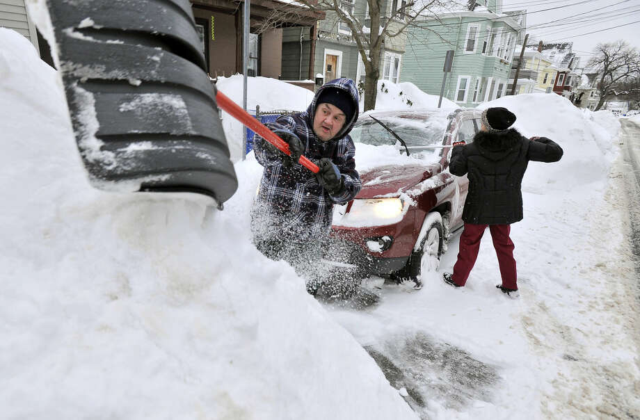 Rich and Kathy Melvin shovel out their car in front of their house in Somerville,, Mass., Tuesday, Feb. 10, 2015. The latest snowstorm left the Boston area with another two feet of snow and forced the MBTA to suspend all rail service for the day. (AP Photo/Josh Reynolds)
