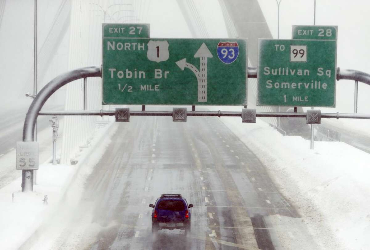 A lone car drives over the Zakim Bridge in Boston, Sunday, Feb. 15, 2015. A storm brought a new round of wind-whipped snow to New England on Sunday, accompanied by near-whiteout conditions and lightning strikes in coastal areas as people contended with a fourth winter onslaught in less than a month. (AP Photo/Michael Dwyer)