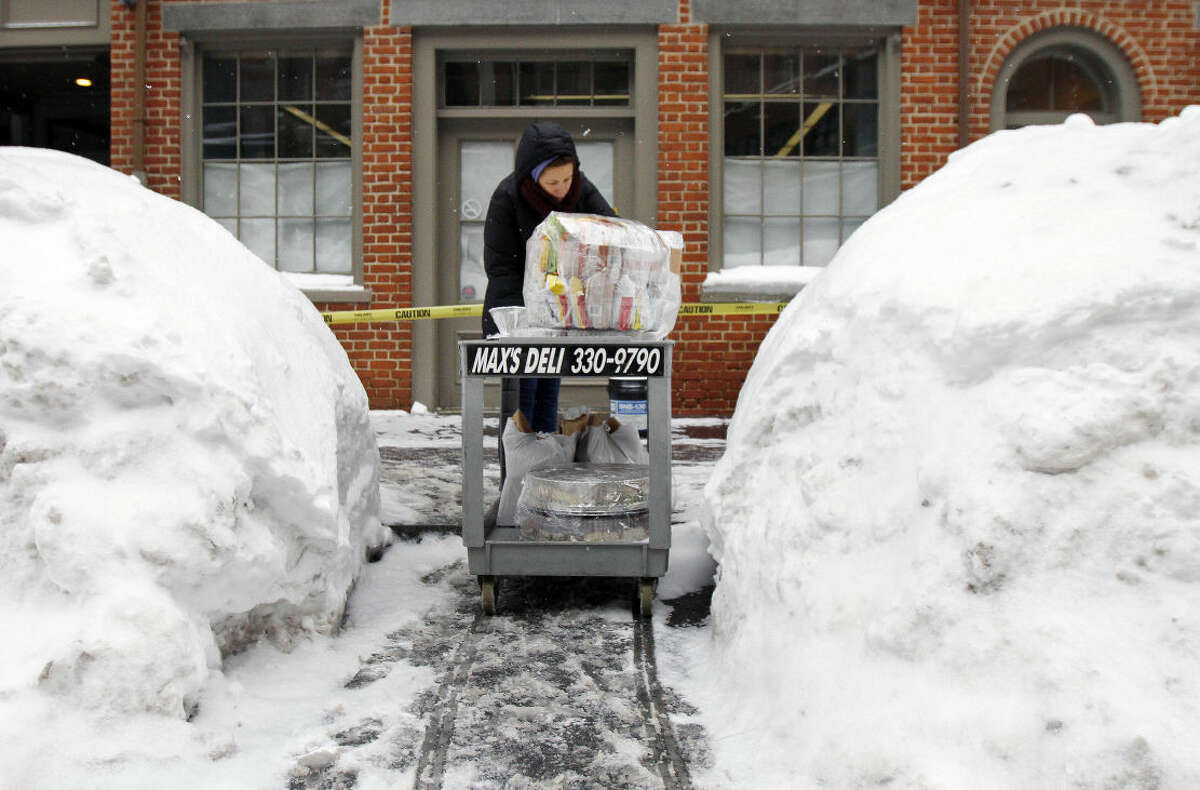 A person delivers lunch through a snowy street, Wednesday, Feb. 11, 2015, in downtown Boston. With streets boxed in by mountains of snow, delivery drivers in the region are struggling to deliver daily supplies to downtown stores, as well as Valentine's Day flowers and edibles. (AP Photo/Bill Sikes)