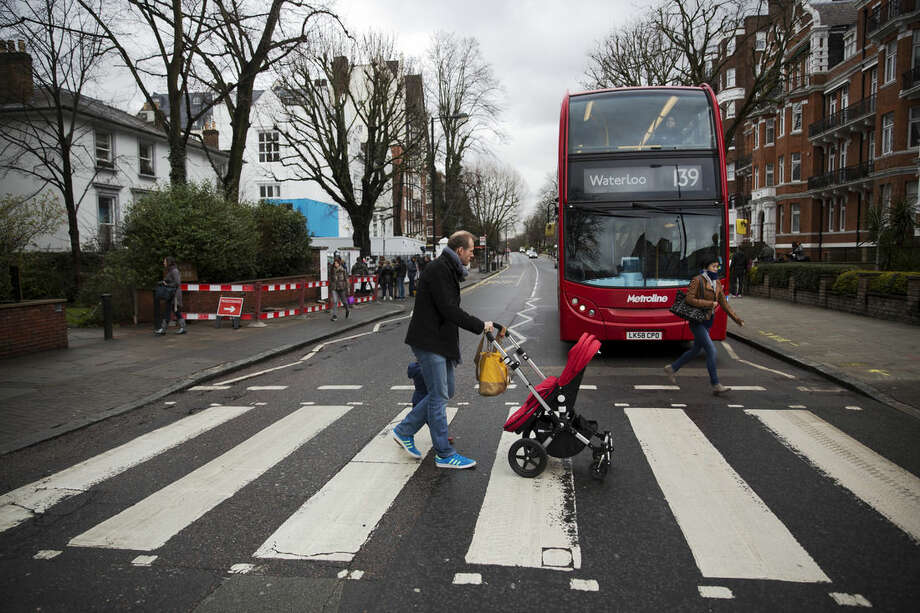 People walk over the zebra crossing where the cover picture of the Beatles' Abbey Road album was taken outside Abbey Road studios in London, Wednesday, March 9, 2016. George Martin, the Beatles' urbane producer who quietly guided the band's swift, historic transformation from rowdy club act to musical and cultural revolutionaries, has died, his management said Wednesday. He was 90. (AP Photo/Matt Dunham)