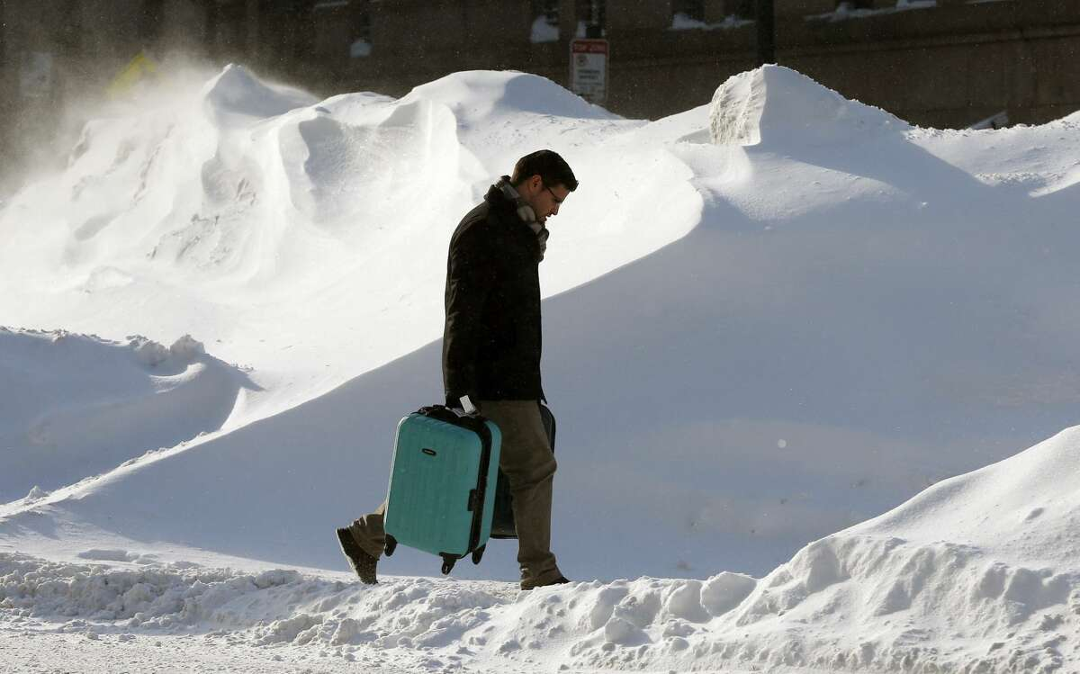 A man carries luggage past giant snow banks in Boston, Sunday, Feb. 15, 2015. A storm brought a new round of wind-whipped snow to New England on Sunday, threatening white-out conditions in coastal areas and forcing people to contend with a fourth winter onslaught in less than a month. (AP Photo/Michael Dwyer)