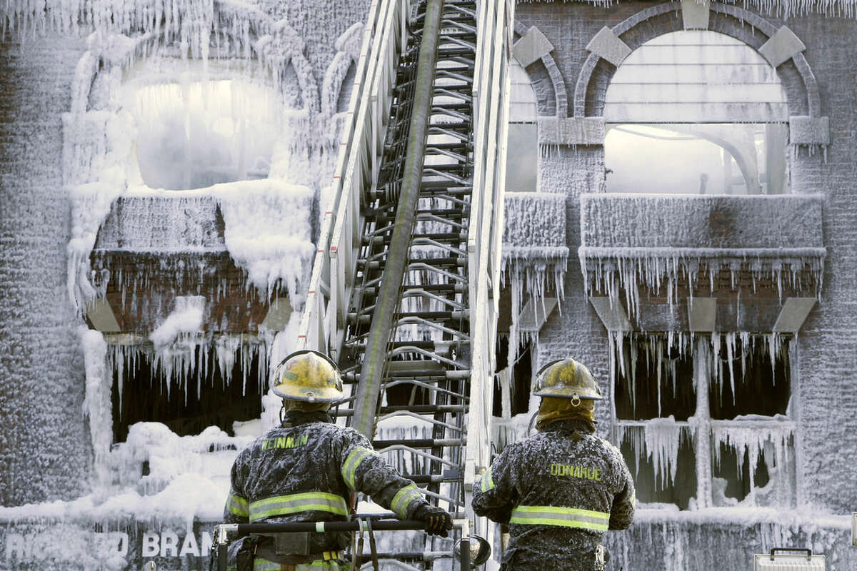 Philadelphia firefighters work the scene of an overnight blaze in west Philadelphia, Monday Feb. 16, 2015, as icicles hang from where the water from their hoses froze. Bone-chilling, single digit temperatures have gripped the region, prompting the closure of all parish and regional Catholic elementary schools in the city of Philadelphia. (AP Photo/Jacqueline Larma)