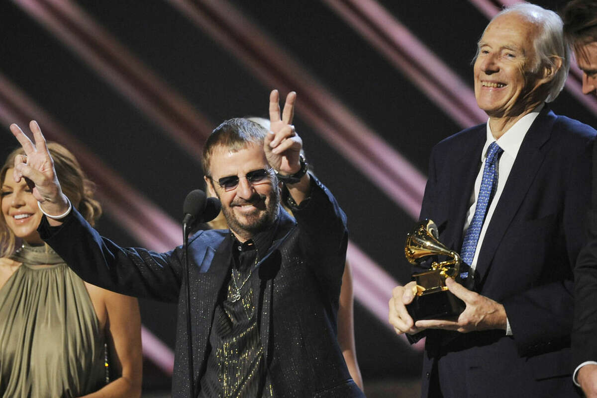 FILE - In this Feb. 10, 2008, file photo, musician Ringo Starr, center, and Beatles producer Sir George Martin accept the best compilation soundtrack album award for