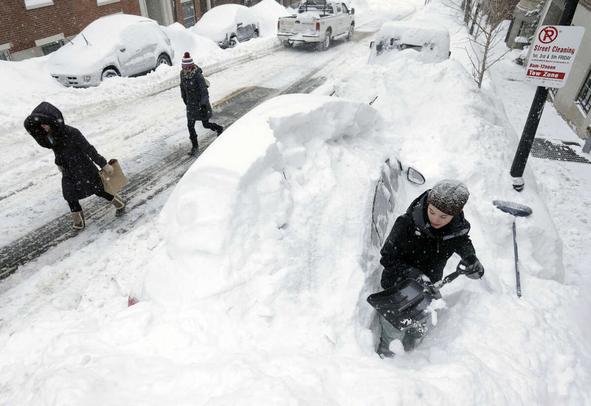 Taylor LaBrecque digs her car out of a snow pile on Beacon Hill Monday, Feb. 9, 2015, in Boston. A long duration winter storm that began Saturday night remains in effect for a large swath of southern New England until the early morning hours Tuesday. (AP Photo/Steven Senne)
