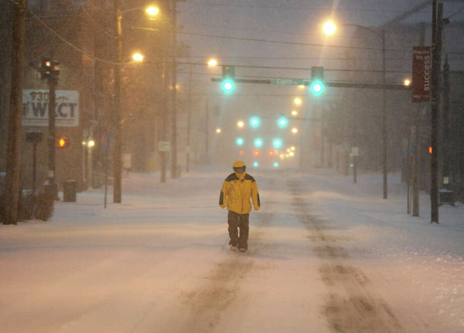 Ron Davis walks to to a doctor appointment early Monday, Feb. 16, 2015 Bowling Green, Ky. The National Weather Service say anywhere from 6 to 15 inches of snow are possible by evening. Bitterly cold temperatures are expected to follow, with lows below zero. (AP Photo/Daily News, Joe Imel)