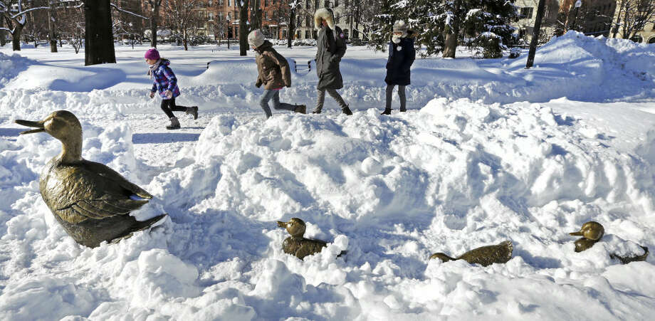 "Children run through the Boston Public Garden, passing the nearly snow covered ""Make Way for Ducklings"" statues, in Boston, Tuesday, Feb. 3, 2015. The Boston area has received about 40 inches of snow in the past week. (AP Photo/Charles Krupa)"