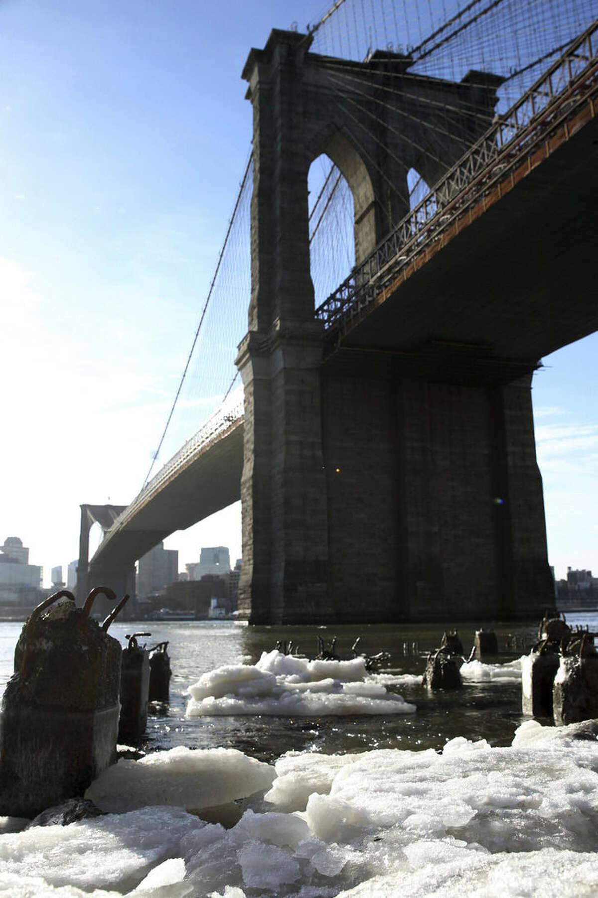 Ice forms under the Brooklyn Bridge on the Manhattan side of the East River in New York on Monday, Feb. 16, 2015. Temperatures in the city were in the single digits on Monday morning. (AP Photo/Peter Morgan)