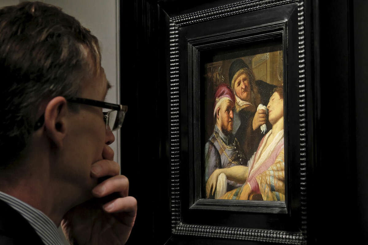 A visitor to the booth of Galerie Talabardon & Gautier at the TEFAF fine art fair looks at a newly discovered painting by Dutch master Rembrandt titled The Unconscious Patient (Sense of Smell) dated at around 1624-25, oil on panel 21.6x17.8 cm, in Maastricht, southern Netherlands, Thursday, March 10, 2016. (AP Photo/Mike Corder)