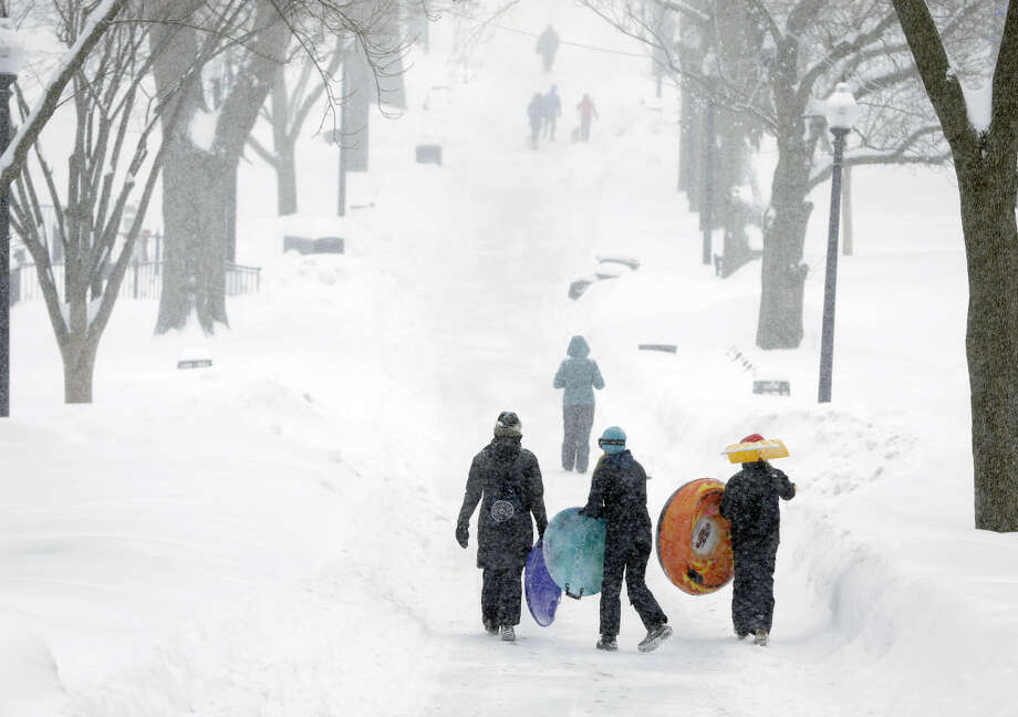 People carry their sleds at the Boston Common, Monday, Feb. 9, 2015, in Boston. The third major winter storm in less than two weeks inflicted fresh snow across New England and portions of New York state on Monday. (AP Photo/Steven Senne)
