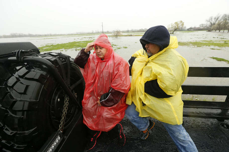 Joe and Mariew Tovar are transported in a Bossier Parish Sheriff truck to return to their home to retrieve belongings during rising floodwaters in in Bossier Parish, La., Thursday, March 10, 2016. A second round of rain early Thursday hit an already inundated north Louisiana, where flooding in some places was up to the rooftops and in others submerged cars, stranded families and forced evacuations. (AP Photo/Gerald Herbert)