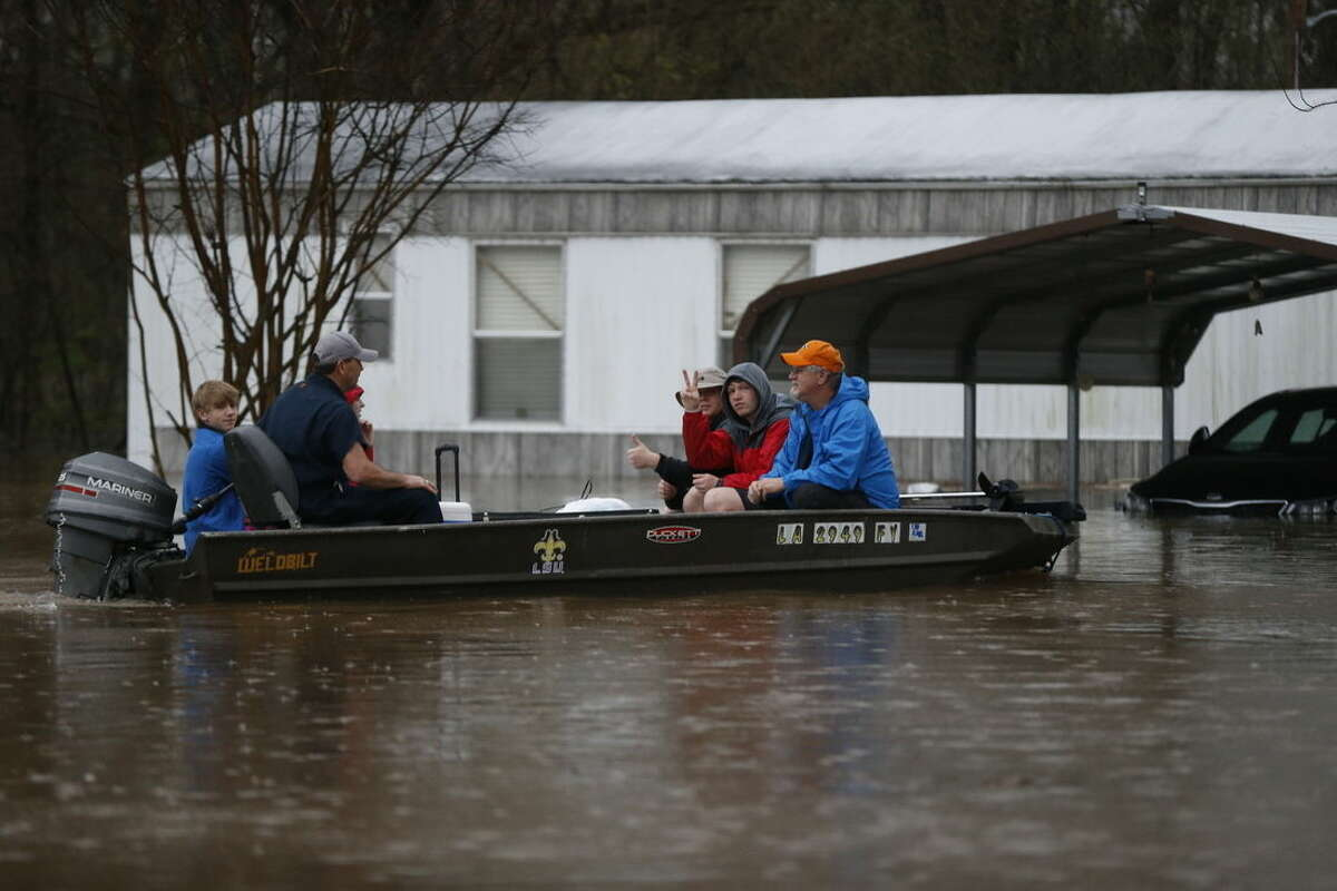 People motor through rising floodwaters at the Pecan Valley Estates trailer park in Bossier City, La., Wednesday, March 9, 2016. (AP Photo/Gerald Herbert)