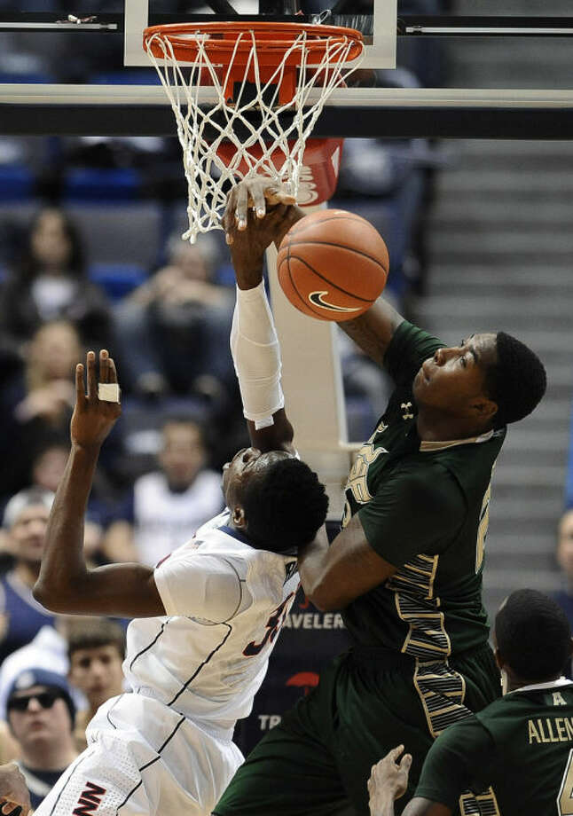 South Florida's Chris Perry, right, stops a shot-attempt by Connecticut's Amida Brimah, left, during the first half of an NCAA college basketball game on Wednesday, Feb. 12, 2014, in Hartford, Conn. (AP Photo/Jessica Hill)