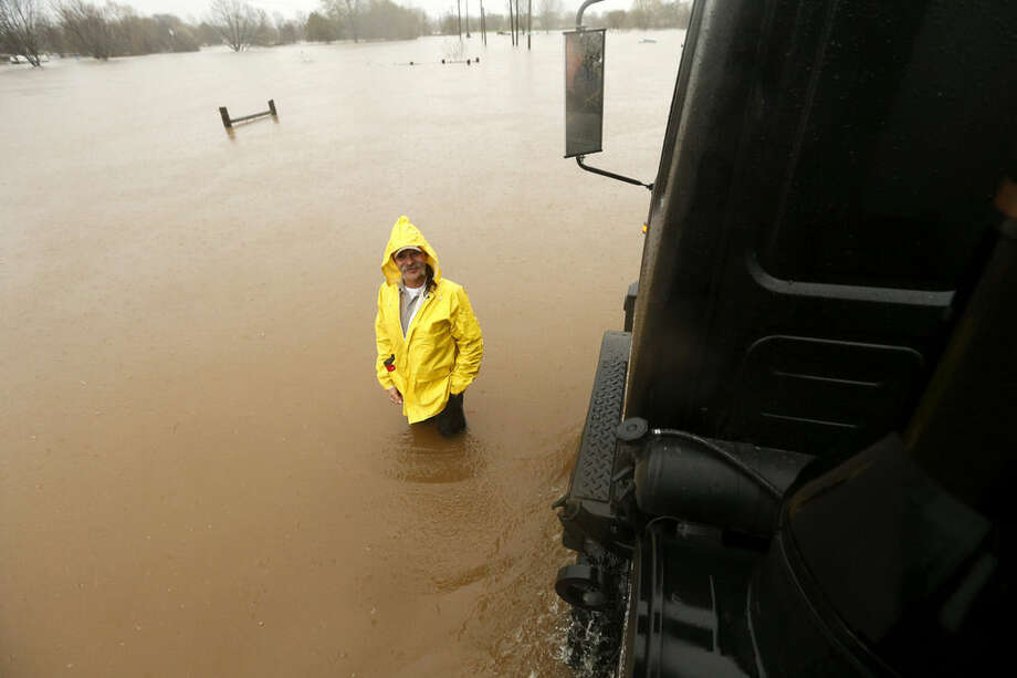 A man stands in rising floodwaters as a Bossier Parish Sheriff truck passes through rising floodwaters in Bossier Parish, La., Thursday, March 10, 2016. A second round of rain early Thursday hit an already inundated north Louisiana, where flooding in some places was up to the rooftops and in others submerged cars, stranded families and forced evacuations. (AP Photo/Gerald Herbert)