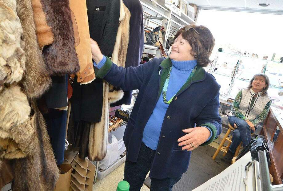 Hour Photo/Alex von Kleydorff Sharon Sobel, President places a womens shearling coat on the rack at the Turnover Shop