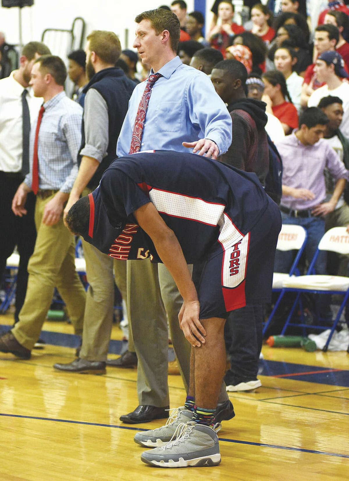 Hour photo/John Nash Brien McMahon's TJ Burden, front, is comforted by Senators head coach Ken Dustin after their team's 53-44 loss to Danbury on Thursday in CIAC Class LL boys basketball second round tournament game.