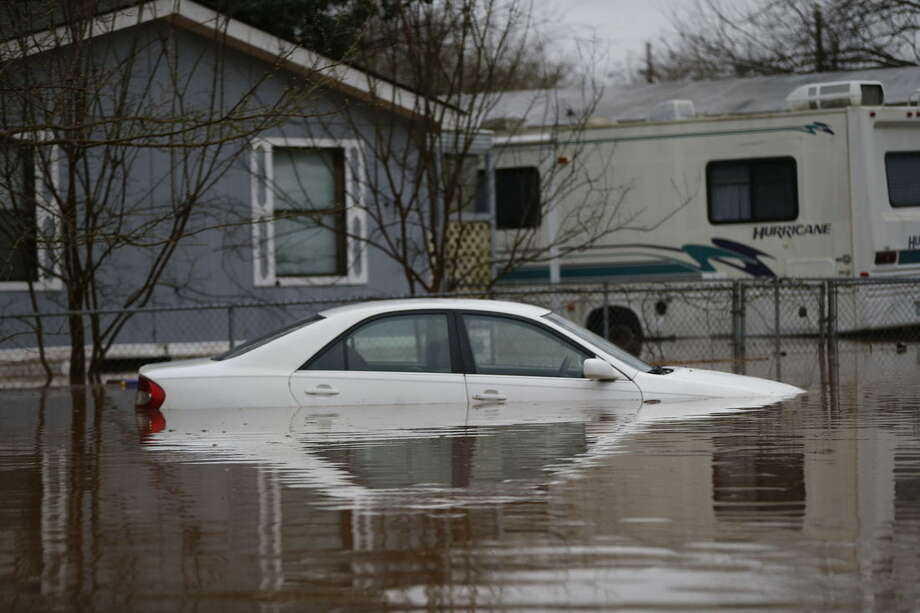 A car is seen partially submerged during rising floodwater at the Pecan Valley Estates trailer park in Bossier City, La., Wednesday, March 9, 2016. (AP Photo/Gerald Herbert)