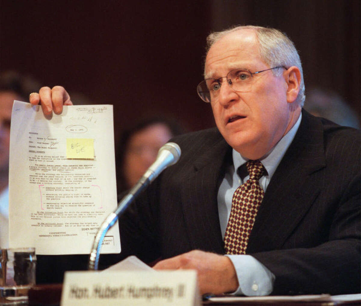 FILE - In this Thursday, May 14, 1998 file photo, Minnesota Attorney General Hubert Humphrey III holds an internal RJR document stating that tobacco causes lung cancer, while testifying on Capitol Hill in Washington before the Democratic Tobacco Task Force. (AP Photo/Khue Bui)