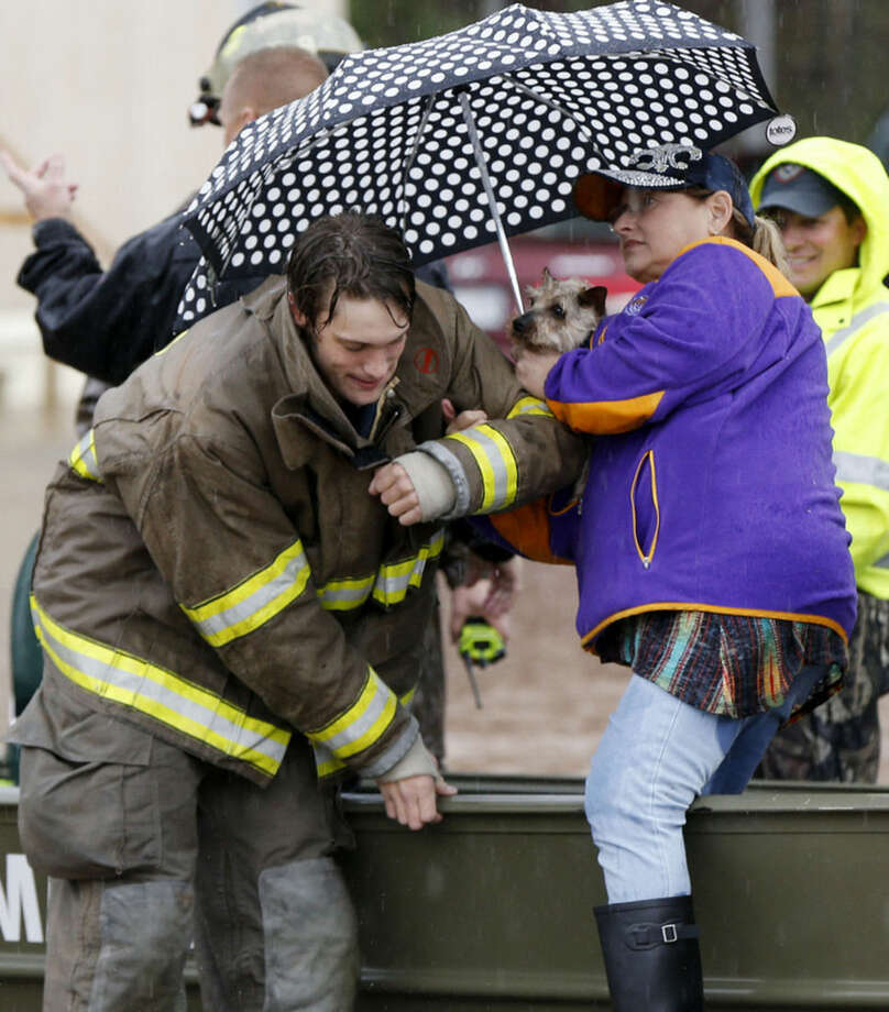 Bossier City Firemen and volunteers help residents evacuate from rising water at the Pecan Valley Estates trailer park in Bossier City, La., Wednesday, March 9, 2016. (AP Photo/Gerald Herbert)