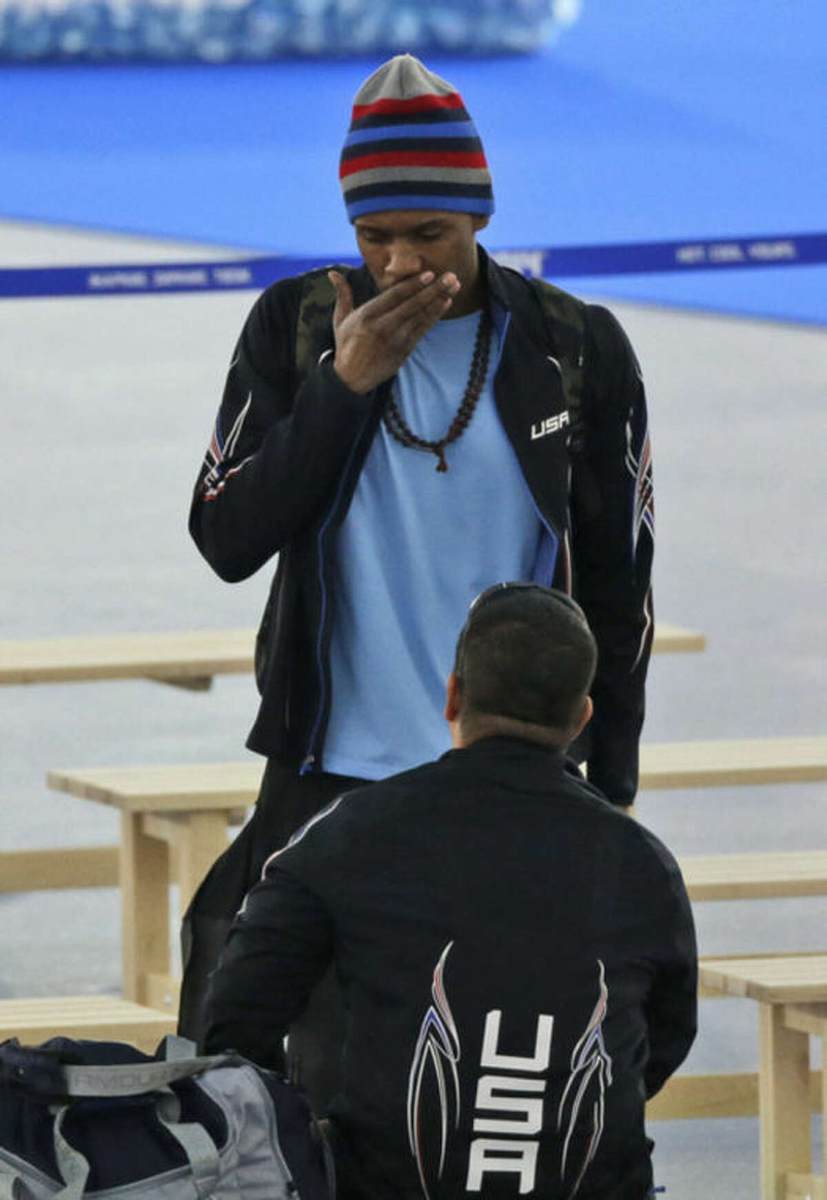 Shani Davis of the U.S. stands with his coach Ryan Shimabukuro and looks downward in dejection after the men's 1,000-meter speedskating race at the Adler Arena Skating Center during the 2014 Winter Olympics in Sochi, Russia, Wednesday, Feb. 12, 2014. (AP Photo/David J. Phillip )