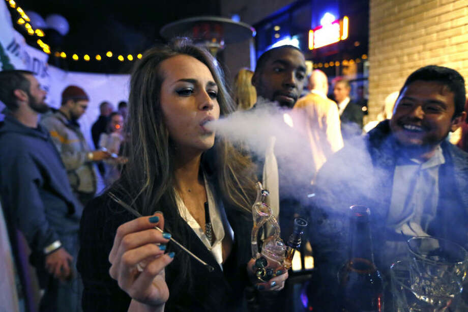 FILE - In this Tuesday evening, Dec. 31, 2013 file photo, a woman smokes marijuana during a Prohibition-era themed New Year's Eve party at a bar in Denver, the day before Colorado allowed retail sales of marijuana to those 21 and over. Polls show that cigarette smoking is no longer considered normal behavior, and is now less popular among teens than marijuana. (AP Photo/Brennan Linsley)
