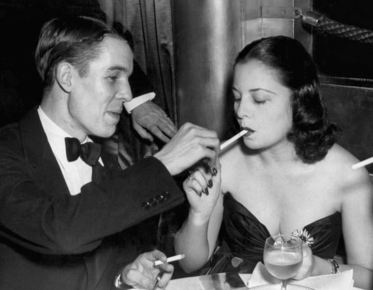 FILE - In this Oct. 16, 1937 file photo, Alfred Gwynne Vanderbilt lights the cigarette of Eleanor Young at the opening of the Sert Room of the Waldorf Astoria in New York. (AP Photo)