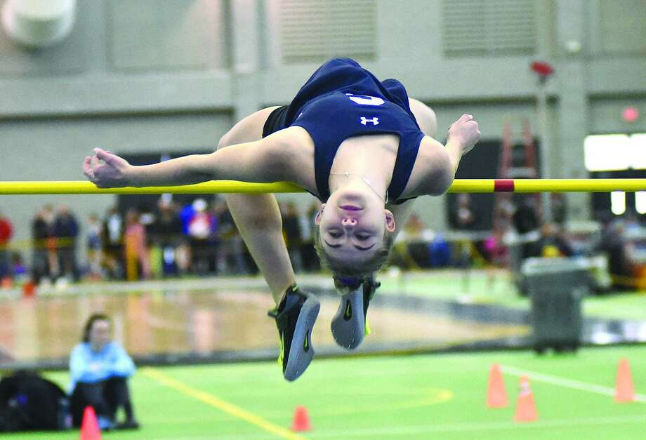Hour photo/John Nash - Staples High high jumper Elizabeth Knoll bends herself over the bar during Monday's CIAC Class LL championship meet in New Haven. Knoll won the event.