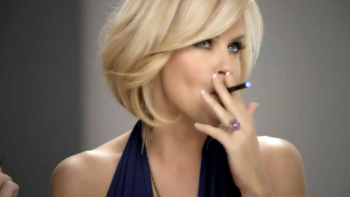 In this undated image from video provided by Resound Marketing in August 2013, Jenny McCarthy uses a blu eCig in a television advertisement. Electronic cigarettes have often been described as a less dangerous alternative to regular cigarettes. But there are few studies exploring exactly what chemicals are in them, and whether they are harmful. Some experts believe that at a time when cigarette smoking has finally become passe in popular culture, e-cigarettes may re-glamorize puffing away in public places. (AP Photo/Resound Marketing)