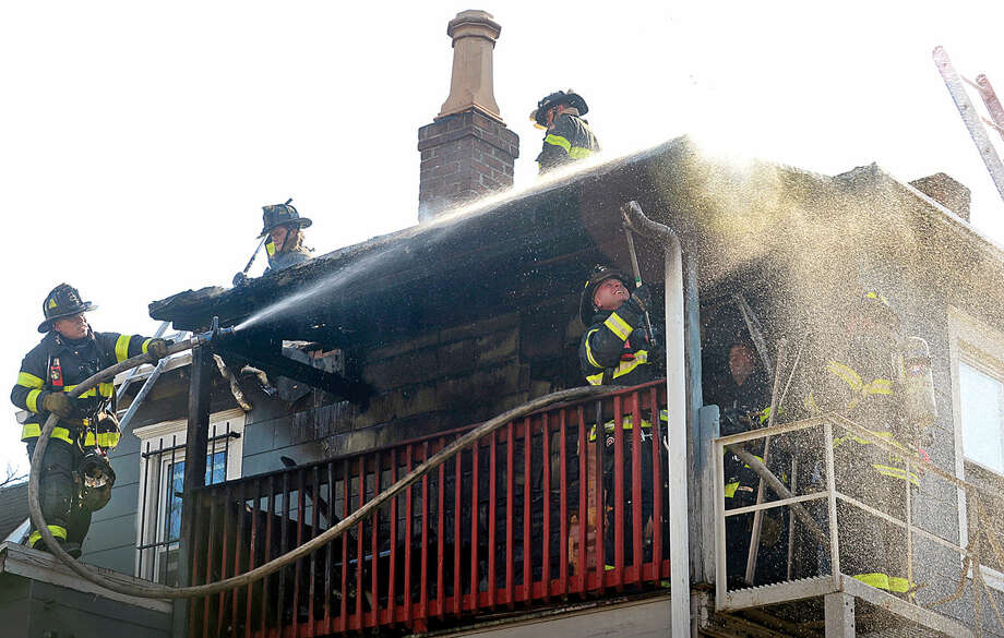 Hour photo / Erik Trautmann Norwalk firefighters battle a fire that engulfed the rear deck of the home at 25 Leuvine Street in Norwalk Tuesday afternoon.