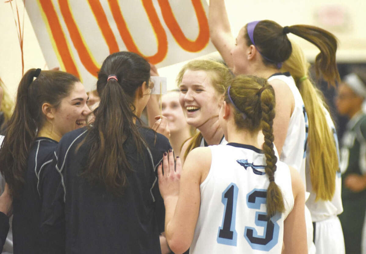 Hour photo/John Nash Wilton's Erin Cunningham, center, is all smiles as she is mobbed by teammates after scoring the 1,000th point of her varsity career against Norwalk on Monday night at the Zeoli Field House.