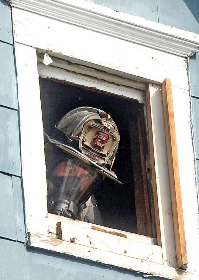 Hour photo / Erik Trautmann A Norwalk firefighter peers out of an attic window he vented while battling a fire that engulfed the rear deck of the home at 25 Leuvine Street in Norwalk Tuesday afternoon.