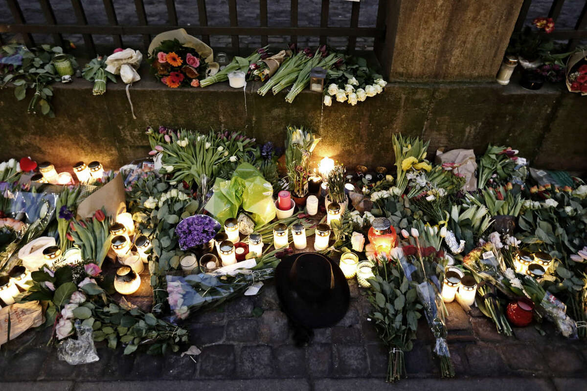 Flowers and candles lay in front of the Jewish Synagogue, in Copenhagen, Monday, Feb. 16, 2015, following the attacks at the weekend. One person was killed and two policemen wounded in front of the Synagogue during this weekend's terror attack in Copenhagen. Danish police shot and killed a man early Sunday suspected of carrying out shooting attacks at a free speech event and then at a Copenhagen synagogue, killing a Danish documentary filmmaker and a member of the Scandinavian country's Jewish community. Five police officers were also wounded in the attacks. (AP Photo/Polfoto, Jens Dresling) DENMARK OUT