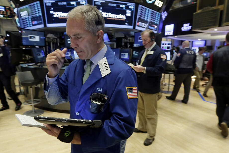 Trader Timothy Nick, left, works on the floor of the New York Stock Exchange, Tuesday, March 8, 2016. Stocks are pulling back in morning trading Tuesday as oil prices slip and energy companies drop sharply. (AP Photo/Richard Drew)