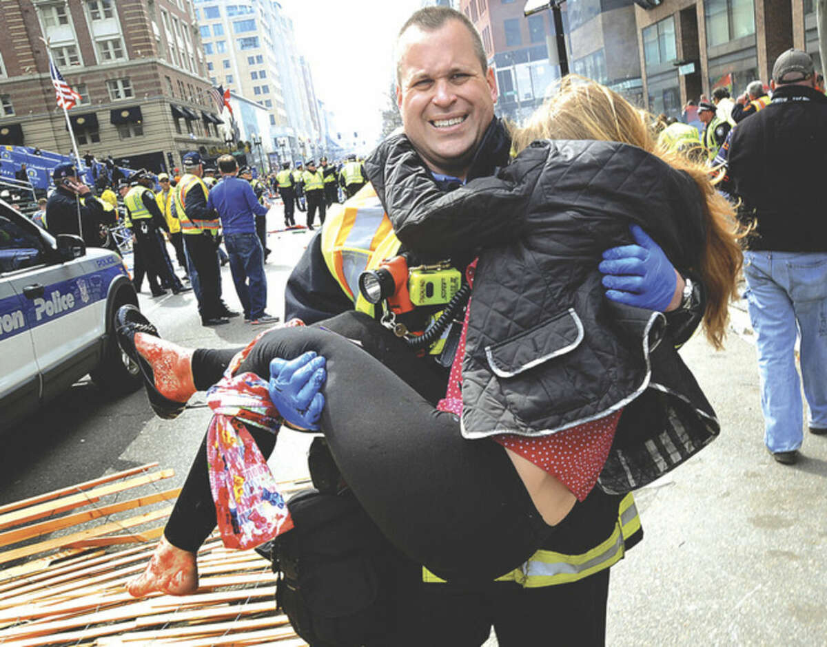 AP file photo/MetroWest Daily News, Ken McGagh In this April 15, 2013 file photo, Boston Firefighter James Plourde carries Victoria McGrath from the scene after a bombing near the Boston Marathon finish line.