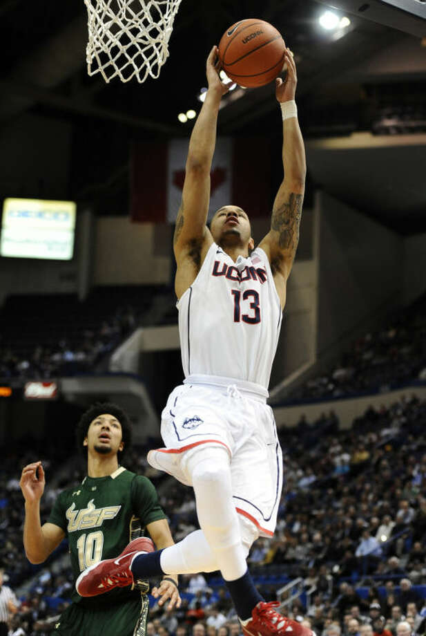 Connecticut's Shabazz Napier (13) scores a basket as South Florida's Josh Heath, left, defends during the first half of an NCAA college basketball game on Wednesday, Feb. 12, 2014, in Hartford, Conn. (AP Photo/Jessica Hill)