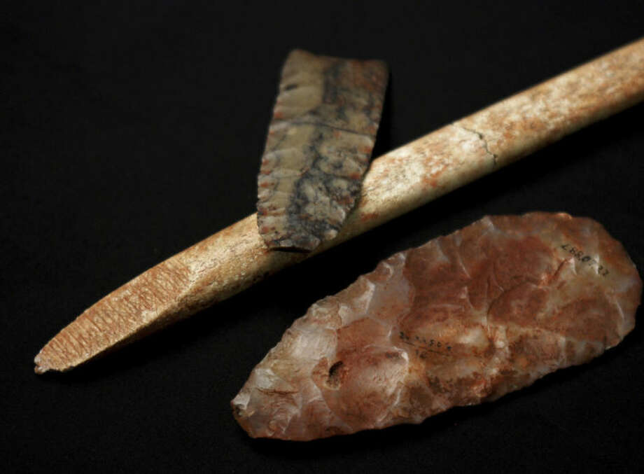 This undated photo provided by researcher Sarah L. Anzick shows a nearly-complete projectile point, top, a mid-stage point made of translucent quartz and an end-beveled rod of bone from a Clovis-era burial site found in 1968 in western Montana. Scientists have recovered and analyzed the DNA of an infant who died more than 12,000 years ago and was buried at the site where these artifacts were found. By comparing the boy's genome to those of present-day people, the research showed that many of today's Native Americans are direct descendants of the population the boy belonged to, and that he is closely related to all indigenous American populations, especially in Central and South America, the researchers said. The DNA analysis was reported online Wednesday, Feb. 12, 2014 in the journal Nature. (AP Photo/Sarah L. Anzick)
