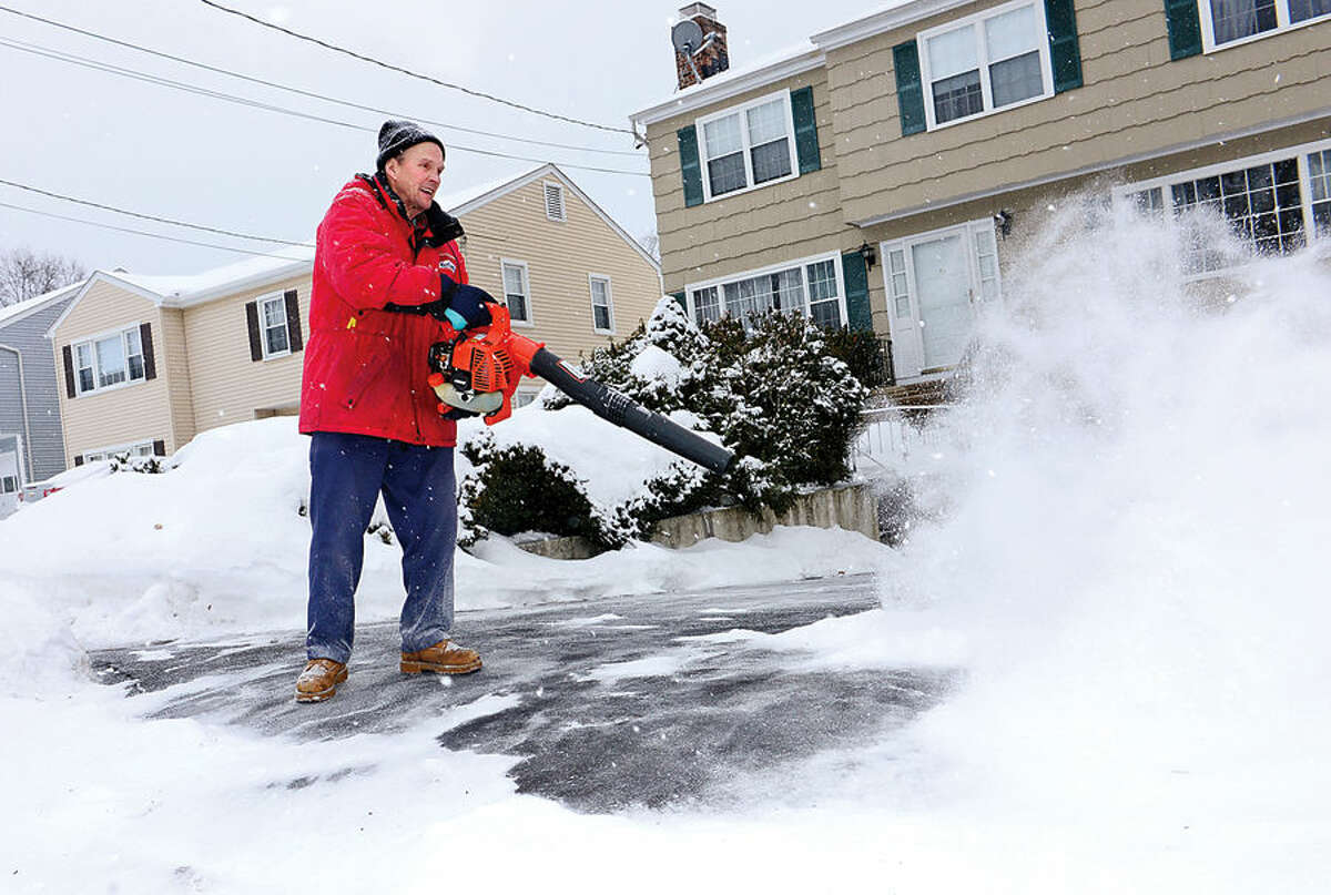 Hour photo / Erik Trautmann Norwalk resident Greg Dumas deals with the early morning snowfall at his home on Katy Lane Tuesday.
