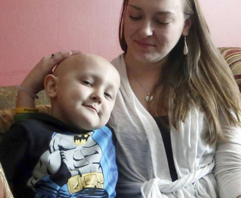FILE - In this Jan. 25, 2016, file photo, Dorian Murray relaxes with his mom, Melissa, at their home in Westerly, R.I. The 8-year-old boy with a rare and untreatable form of terminal pediatric cancer, who told his father he wanted to be famous in China, died Tuesday, March 8, 2016. (Grace White/The Westerly Sun via AP, File) MANDATORY CREDIT.
