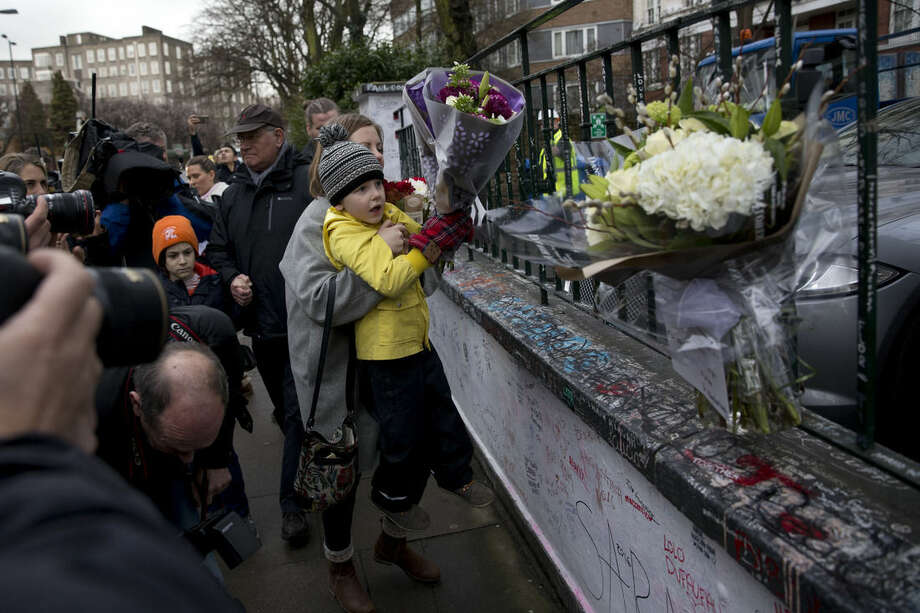 Tourists from Finland place flowers in memory of George Martin, the Beatles' producer, outside Abbey Road studios where the Beatles recorded albums and where the zebra crossing cover picture of the Abbey Road album was originally taken, in London, Wednesday, March 9, 2016. George Martin, the Beatles' urbane producer who quietly guided the band's swift, historic transformation from rowdy club act to musical and cultural revolutionaries, has died, his management said Wednesday March 9, 2016. He was 90. (AP Photo/Matt Dunham)