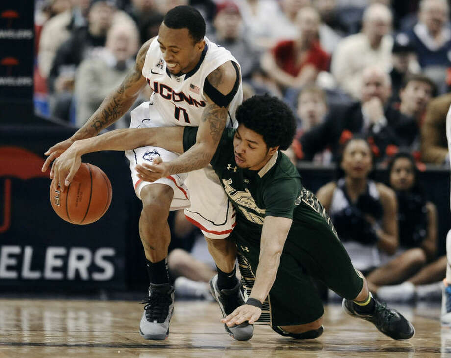 Connecticut's Ryan Boatright , left, steals the ball from South Florida's Josh Heath, right, during the first half of an NCAA college basketball game on Wednesday, Feb. 12, 2014, in Hartford, Conn. (AP Photo/Jessica Hill)